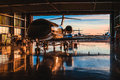 Servicing business aviation at a hangar in backlight sunset Stock Photo