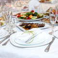 Serviette on a plate on the holiday table served with various dishes Royalty Free Stock Photos
