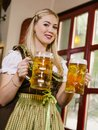 Serving beer at oktoberfest photo of a beautiful female waitress wearing traditional dirndl and holding huge beers in a pub Royalty Free Stock Photo