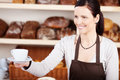 Serving coffee in a bakery friendly young woman an apron hot cup of against backdrop of specialist loaves of bread Stock Photo