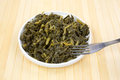 Serving of collard greens in a dish with fork Royalty Free Stock Photo