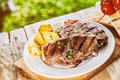 Serving of grilled lamb chops and potato at a bbq garnished with chopped fresh herbs on rustic wooden picnic table in the garden Stock Image