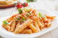 Serving of spicy savory italian penne pasta garnished with fresh basil and topped with grated parmigiano reggiano or parmesan Royalty Free Stock Image
