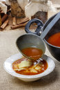 Serving tomato soup. Pouring soup in a plate Royalty Free Stock Photo