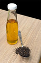 Sesame oil and black sesame seeds in the spoon on wooden table bottle Stock Photos