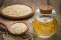 Sesame oil in glass jar and sesame seeds on wooden spoon Royalty Free Stock Photo