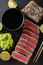 Sesame Seed Crusted Seared Tuna served with wasabi and sauce closeup. Top view vertical Royalty Free Stock Photo