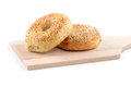 Sesame seed and poppy seed bagel on wooden cutting board Royalty Free Stock Image