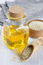 Sesame seeds and oil in a glass bottle on a wooden background Royalty Free Stock Photos