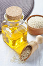 Sesame seeds and oil in a glass bottle on a wooden background Stock Photo