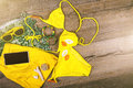 Set of beach clothes yellow bikini, bracelets, shorts, glasses on dark wooden background. Top view. Summer Holiday Royalty Free Stock Photo