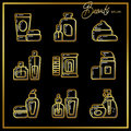 Set of beauty cosmetics icons drawn in gold lines on a black bac