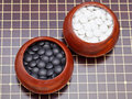 Set of black and white go game stones in wooden bowls Stock Photo