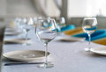 Set of clean empty wine glasses and plates on a dining table with colorful chairs on a restaurant interior pastel background. A cl Royalty Free Stock Photo