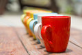 Set of colorful mug cups on a old wooden table Royalty Free Stock Photo