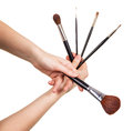 Set  cosmetic brushes in female hands isolated on white background. Royalty Free Stock Photo