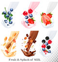 Set of different milk splashes with fruit, nuts and berries. Royalty Free Stock Photo