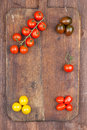 Set different varieties cherry tomatoes dark wooden background Royalty Free Stock Photography