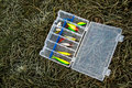 Set of fishing lures in tackle box on frozen grass. Royalty Free Stock Photo