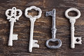 Set of four antique keys one being different and upside down on wood background Royalty Free Stock Image