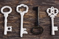Set of four antique keys, one being different and upside down Royalty Free Stock Photo