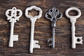 Set of four antique keys one being different on wood background Stock Photography