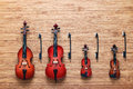 Set of four toy string musical orchestra instruments: violin, cello, contrabass, viola on a wooden background. Music concept. Royalty Free Stock Photo
