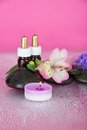 Set of fragrant oils salt candles and flower stones on a pink background Stock Photography