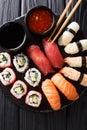 Set of fresh maki, uramaki and nigiri sushi, served on black plate. Vertical top view Royalty Free Stock Photo
