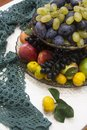 stock image of  A set of fruits in a bunk vase - black and yellow grapes, plums, tangerines, apples