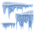 Set of hanging thawing icicles of a blue shade and melting dripping as shiny crystal glass with crisp spikes in icy winter season Stock Photography