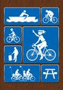 Set icons of rowing boat, family ride, bicycle, roasting area. Icons in blue color on wooden background. Royalty Free Stock Photo