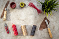 Set of leather craft tools on grey stone background top view copyspace