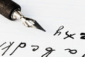 Set of letters and black ink nib of drawing pen on white sheet notebook Royalty Free Stock Photo