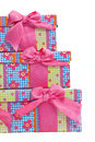 Set of matched colorful party gifts in pretty patterned boxes tied with pink ribbon and bows in three sizes isolated on white for Royalty Free Stock Photo
