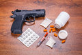 Set of narcotics and handgun on wooden table Stock Photography