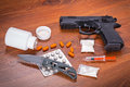 Set of narcotics and handgun on wooden table Royalty Free Stock Photo