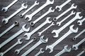 Set of chromed wrenches on a dark wooden workbench. top view Royalty Free Stock Photo