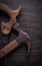 Set of rusted handsaw and claw hammer on wooden board Royalty Free Stock Images
