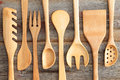 Set of rustic wooden handcrafted kitchen utensils with a spaghetti strainer spoons spatula and salad servers arranged in an Royalty Free Stock Images