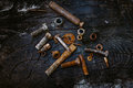 Set of rusty screws, nuts and small tools on a dark wooden background. Royalty Free Stock Photo