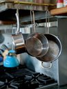 Set of sauce pans hanging to the right of a stove top in a nice kitchen with a stainless steel backsplash and a tea kettle Royalty Free Stock Photo