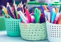 Colored pencils, pens, basket with flowers, watercolor paints and other items on wooden desk. Back to school concept. Royalty Free Stock Photo