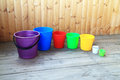 Set from seven colorful buckets for cleaning colourful on a wooden background Stock Image