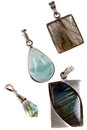 A set of silver pendants made with gemstones like aquamarine labadorite and diamond on white studio background Royalty Free Stock Photo