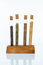 Set of spices in a glass flasks four standing wooden stand on white background Royalty Free Stock Photo