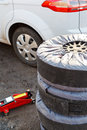 Set of summer car tyres seasonal replacement with jack outdoors Royalty Free Stock Photography