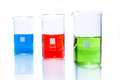 Set of temperature resistant cylindrical beakers with color liquid on white Stock Photos