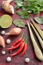 Set of thai ingredients on wooden background red chilli pepper lemongrass fresh lime shallot galangal coriander leaves and white Stock Images