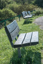 Set of three benches at paths edge in park Royalty Free Stock Photo
